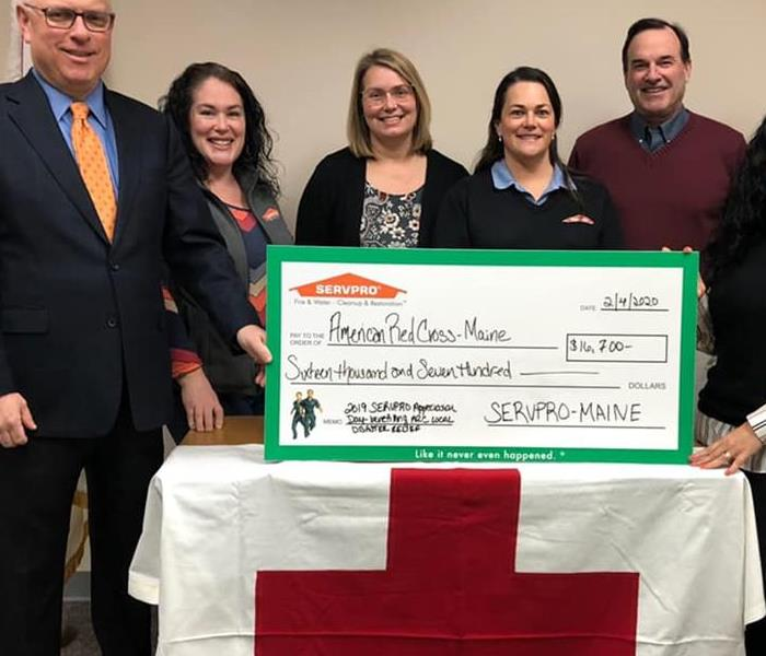 7 people presenting a check